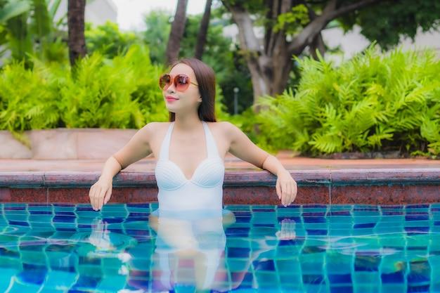 Retrato linda jovem asiática relaxando, sorrindo, relaxando ao redor da piscina ao ar livre