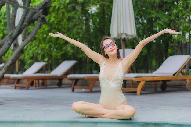 Retrato linda jovem asiática relaxando sorriso ao redor da piscina