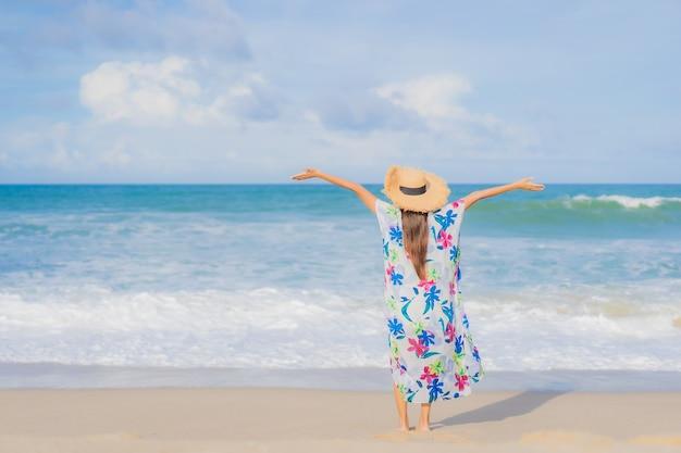 Retrato linda jovem asiática relaxando sorriso ao redor da praia, mar, oceano, nas férias