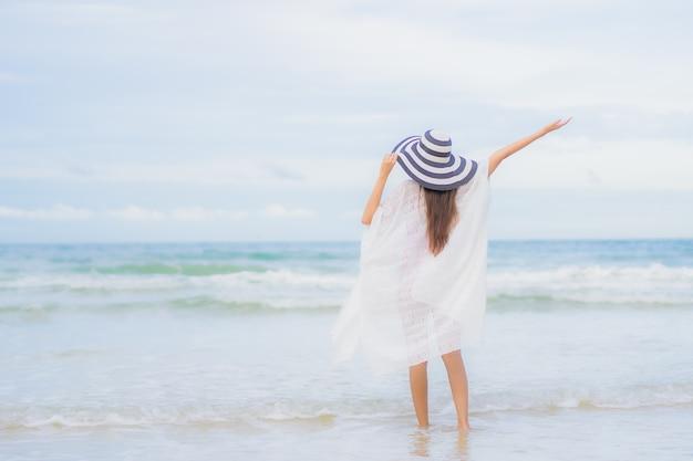 Retrato linda jovem asiática relaxando sorriso ao redor da praia, mar, oceano, numa viagem de férias de férias