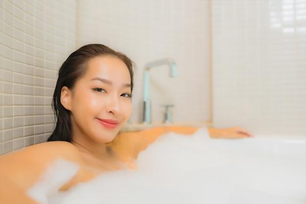 Retrato linda jovem asiática relaxando sorriso na banheira no interior do banheiro