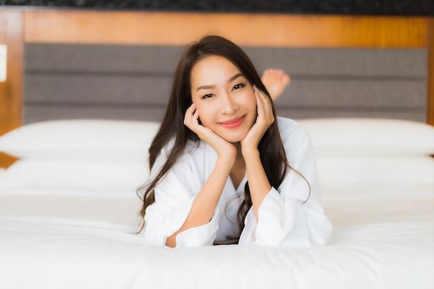Retrato linda jovem asiática relaxando sorriso na cama, no interior do quarto