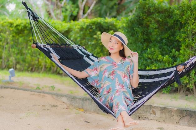 Retrato linda jovem asiática sentada na rede balançando ao redor da praia, mar, oceano, em férias de férias