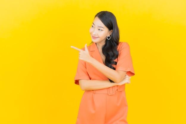 Retrato linda jovem asiática sorrindo com ação em amarelo Foto gratuita