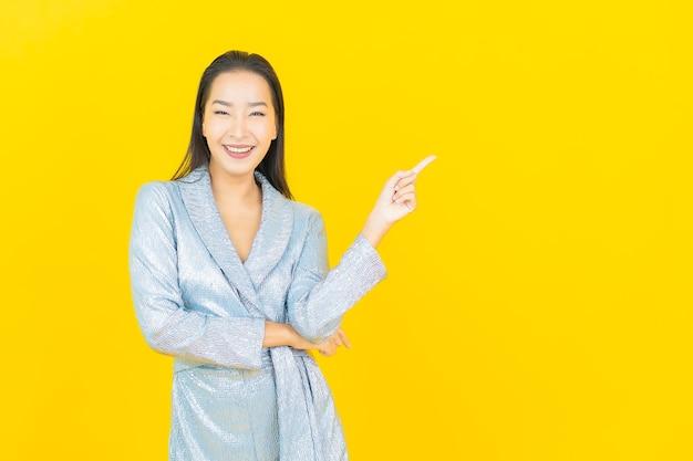 Retrato linda jovem asiática sorrindo com ação na parede amarela