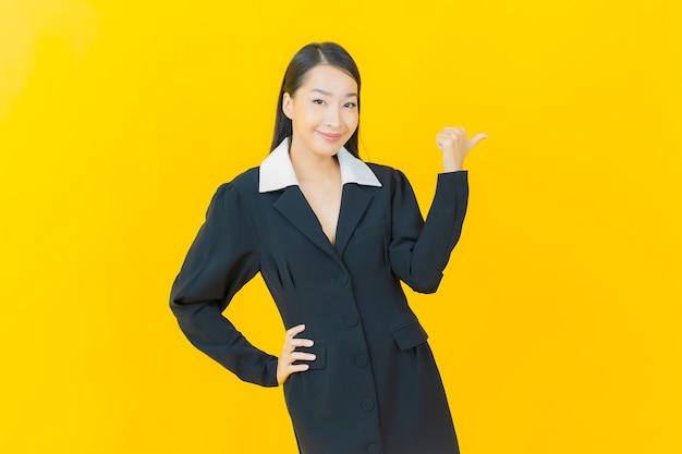 Retrato linda jovem asiática sorrindo com ação na parede colorida