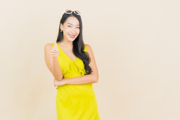 Retrato linda jovem asiática sorrindo com ação na parede creme