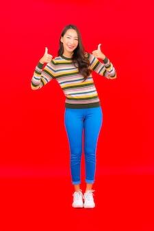 Retrato linda jovem asiática sorrindo com ação na parede vermelha isolada