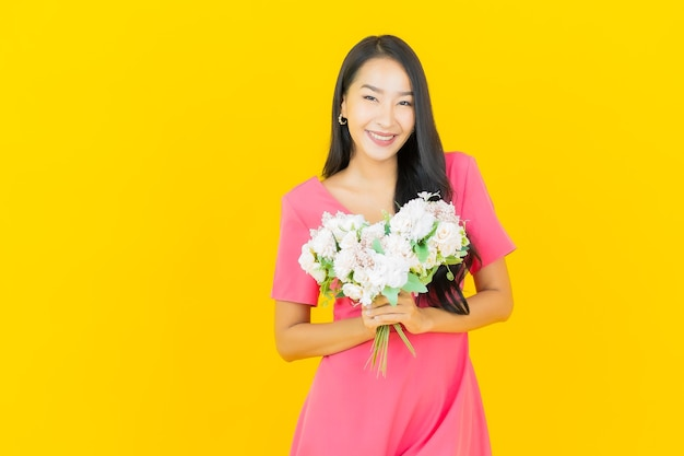 Retrato linda jovem asiática sorrindo com buquê de flores na parede amarela
