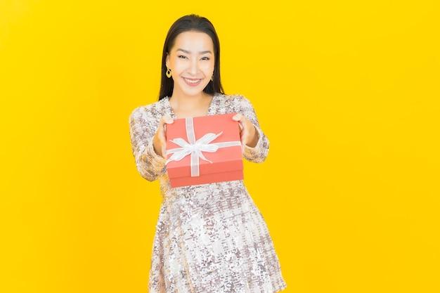 Retrato linda jovem asiática sorrindo com caixa de presente vermelha em amarelo