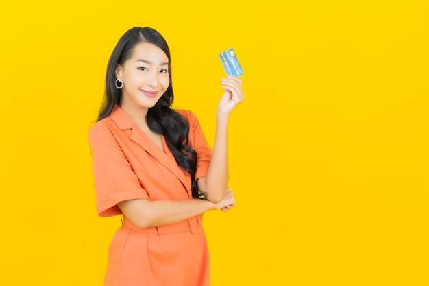 Retrato linda jovem asiática sorrindo com cartão de crédito em amarelo