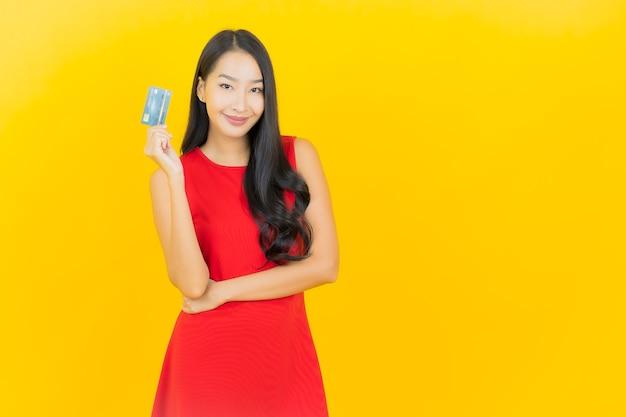 Retrato linda jovem asiática sorrindo com cartão de crédito na parede amarela