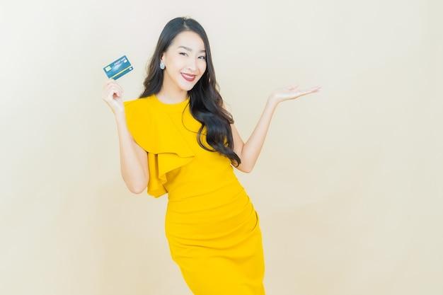 Retrato linda jovem asiática sorrindo com cartão de crédito na parede bege