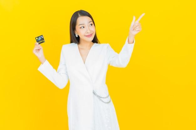 Retrato linda jovem asiática sorrindo com cartão de crédito