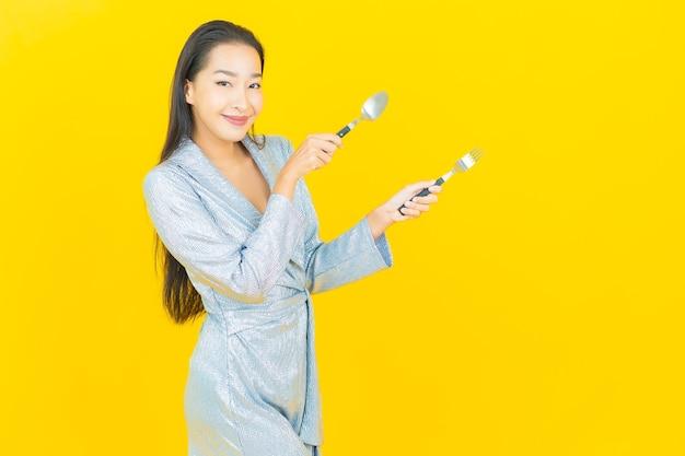 Retrato linda jovem asiática sorrindo com colher e garfo na parede amarela