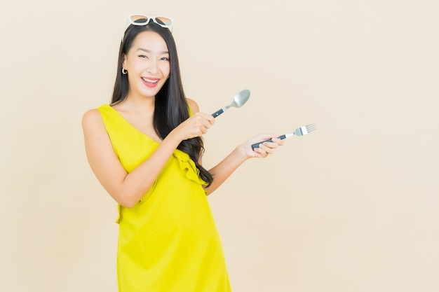 Retrato linda jovem asiática sorrindo com colher e garfo na parede colorida