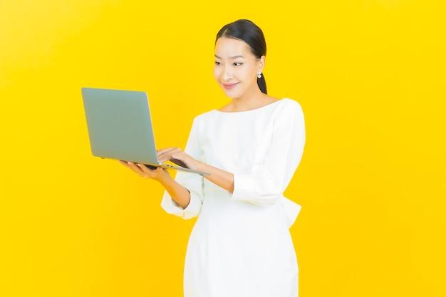 Retrato linda jovem asiática sorrindo com computador laptop em amarelo