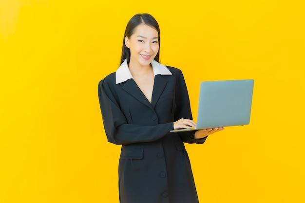 Retrato linda jovem asiática sorrindo com computador laptop na parede isolada