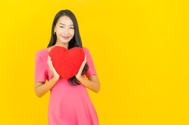Retrato linda jovem asiática sorrindo com formato de almofada em forma de coração na parede amarela.