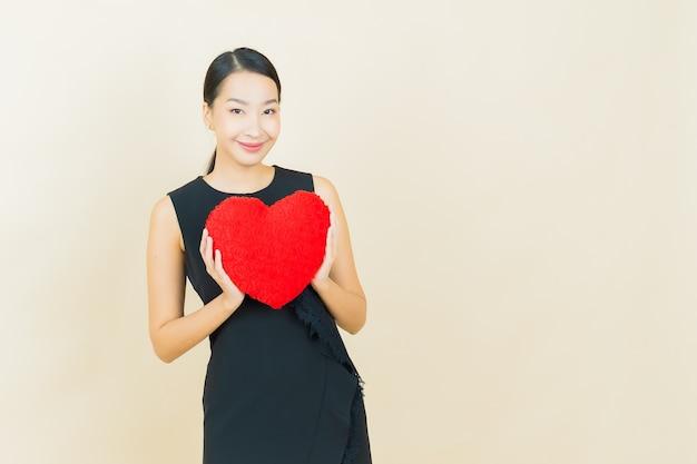 Retrato linda jovem asiática sorrindo com formato de almofada em forma de coração na parede colorida