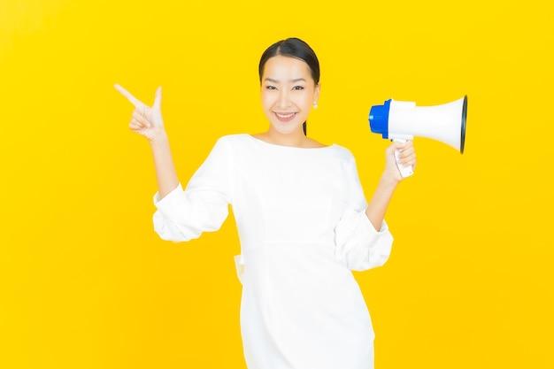 Retrato linda jovem asiática sorrindo com megafone em amarelo