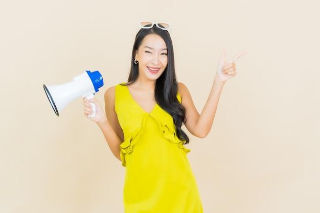 Retrato linda jovem asiática sorrindo com megafone na parede colorida