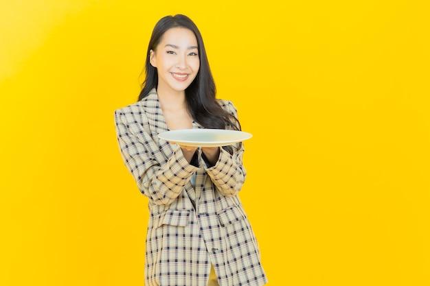 Retrato linda jovem asiática sorrindo com prato vazio