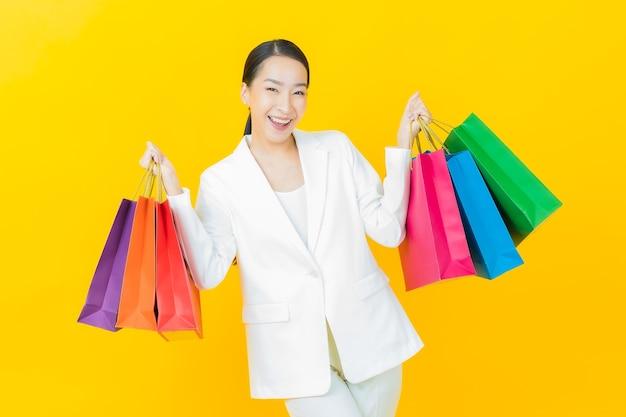 Retrato linda jovem asiática sorrindo com sacolas de compras na parede colorida