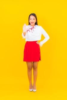 Retrato linda jovem asiática sorrindo em ação em amarelo