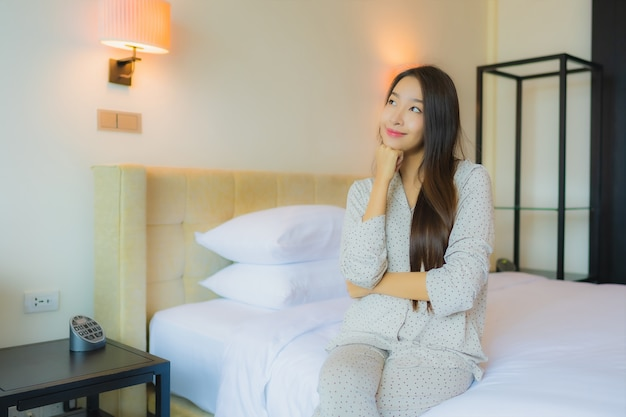 Retrato linda jovem asiática sorrindo feliz relaxando na cama