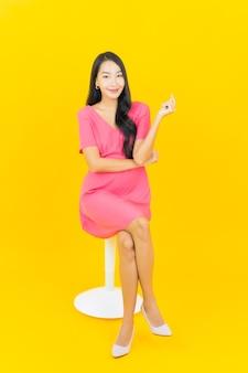 Retrato linda jovem asiática sorrindo na parede amarela