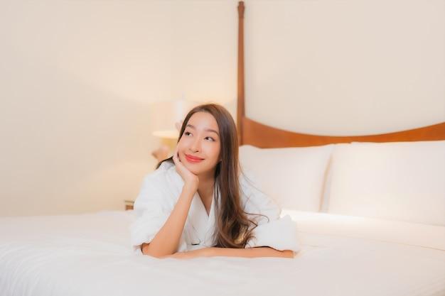 Retrato linda jovem asiática sorrindo relaxando na cama no interior do quarto