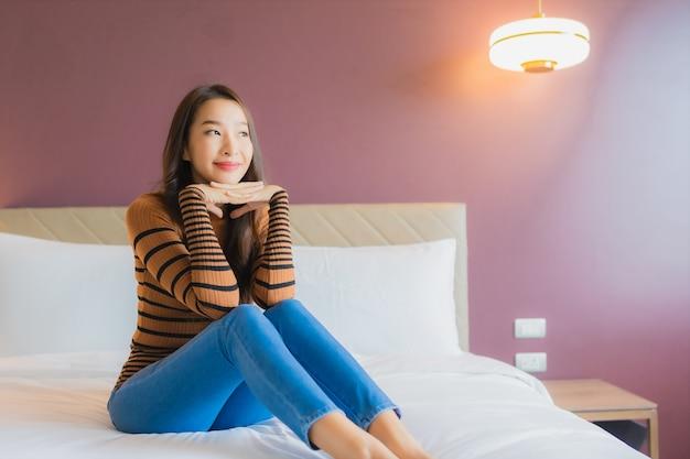 Retrato linda jovem asiática sorrindo relaxando na cama