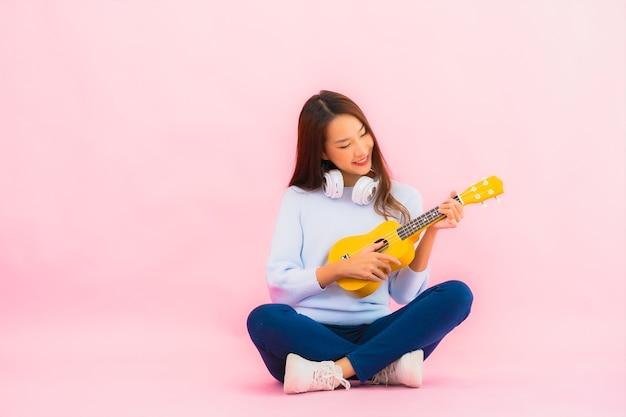 Retrato linda jovem asiática tocando cavaquinho na parede rosa isolada