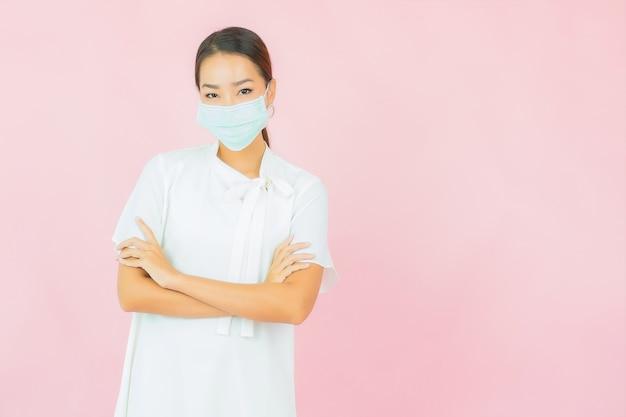 Retrato linda jovem asiática usa máscara para proteger covid19 na parede rosa