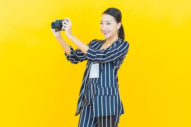 Retrato linda jovem asiática usando câmera na cor de fundo