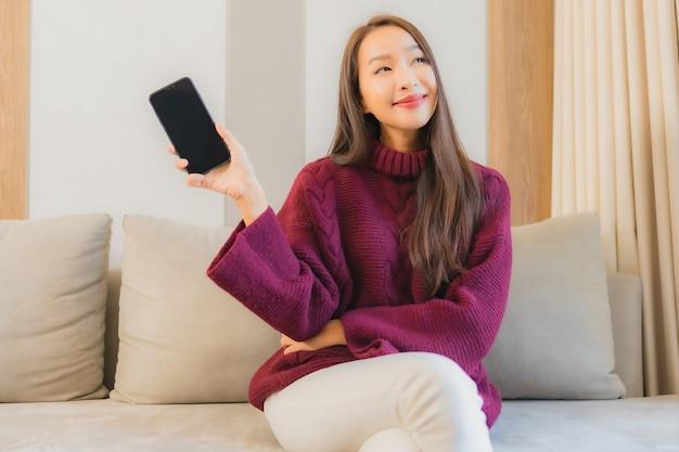 Retrato linda jovem asiática usando celular inteligente no sofá no interior da sala de estar