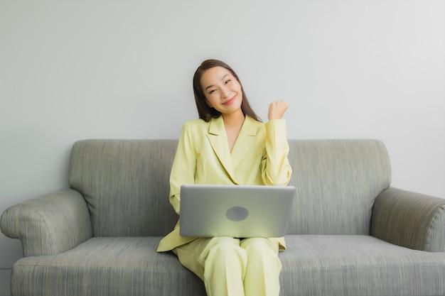 Retrato linda jovem asiática usando computador laptop no sofá no interior da sala de estar