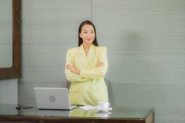 Retrato linda jovem asiática usando computador portátil com celular inteligente na mesa de trabalho na sala interior