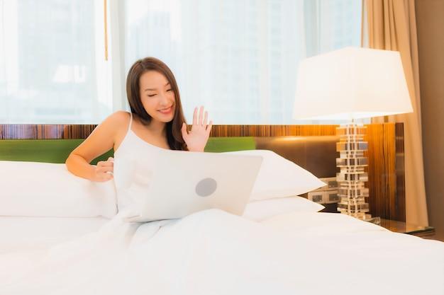 Retrato linda jovem asiática usando laptop na cama no interior do quarto