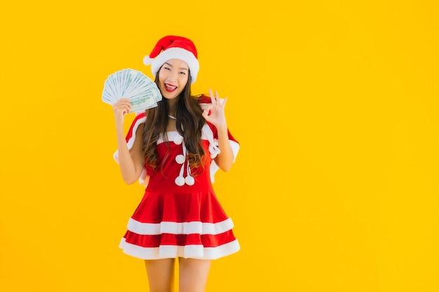Retrato linda jovem asiática usando roupas de natal e chapéu com dinheiro.