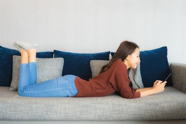 Retrato linda jovem asiática usando telefone inteligente no sofá no interior da sala de estar