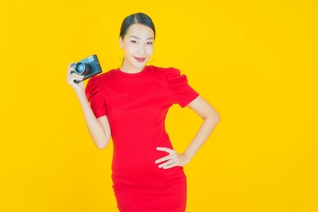 Retrato linda jovem asiática usar câmera em amarelo