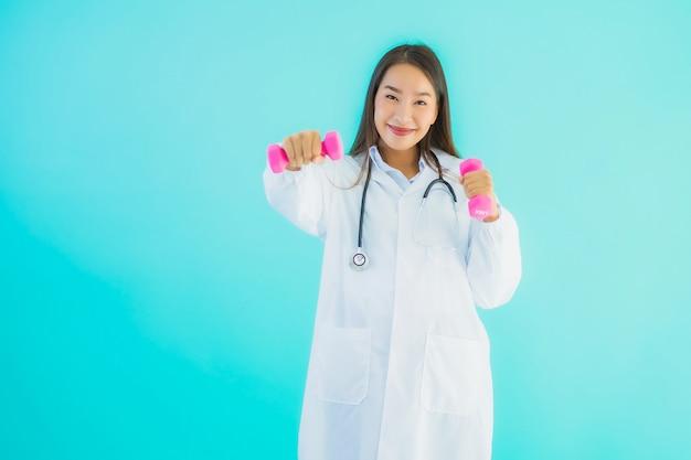 Retrato linda jovem médico asiático mulher com haltere