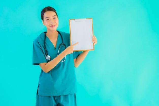 Retrato linda jovem médico asiático mulher com placa de papel vazia para espaço de cópia
