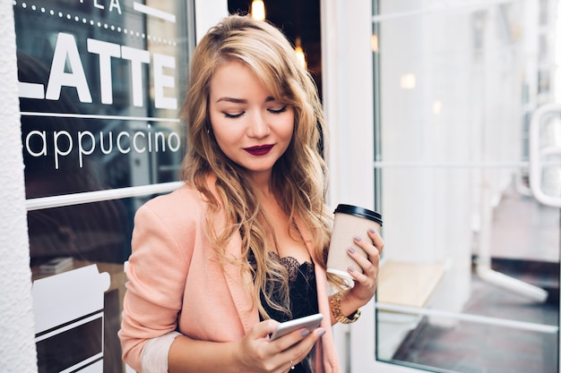 Retrato linda loira no terraço com uma xícara de café. ela usa uma jaqueta coral, lábios carnudos, sorrindo para o telefone na mão.