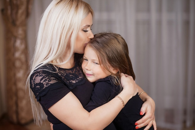 Retrato linda mãe e filha em casa
