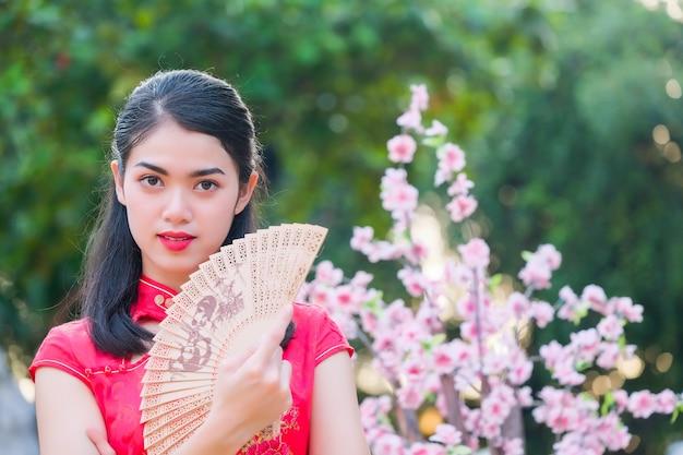 Retrato linda menina asiática com vestido vermelho cheongsam segurar um ventilador