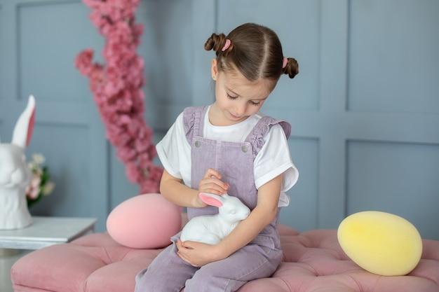 Retrato linda menina brincando com a coelhinha de brinquedo segurando um pequeno fazendeiro coelho