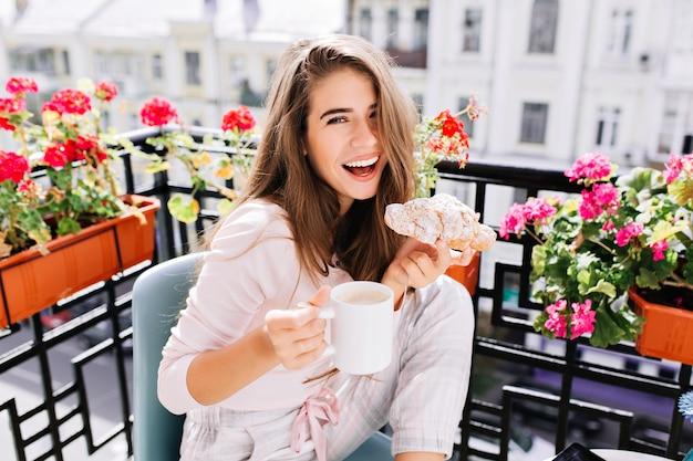 Retrato linda menina com cabelo comprido, tomando café da manhã na varanda pela manhã na cidade. ela segura uma xícara, um croissant, rindo.